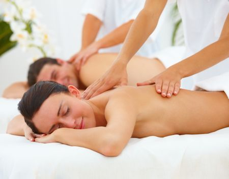 Young man and woman lying on bed and getting massage