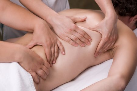 a man is getting massage treatment by two therapists