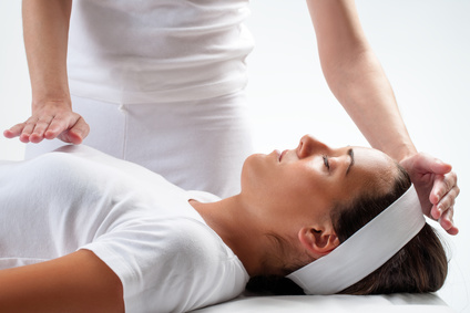 Close up of massage therapist's hands doing reiki on young woman. One hand on head and one hand on chest.