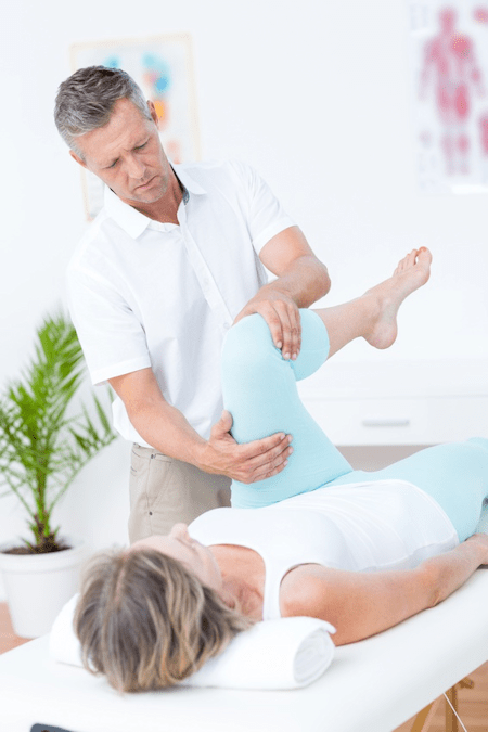 A male physiotherapist performing Trager Approach leg treatment on female patient