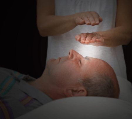 Therapeutic touch treatment - female reiki practitioner's hands over the man's face