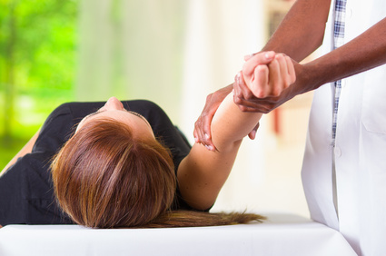 Woman lying down getting physical therapy massage treatment from physio therapist, hands working on her elbow area