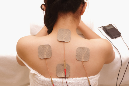 Asian woman is receiving electrical -stimulation ( TENS ) for the neck and back pain