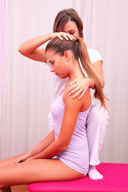 A physiotherapist treating a female patient's neck using Alexander Technique
