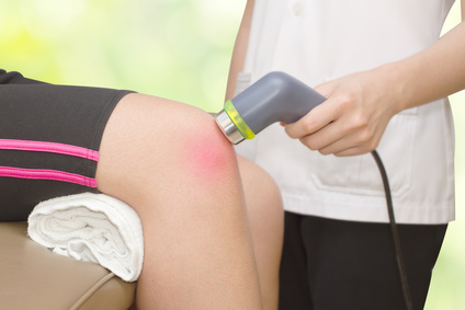 Physical therapist using ultrasound probe on woman patient 's knee for pain and inflamation