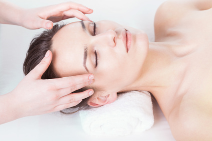 Stressed young woman having head massage at massage clinic