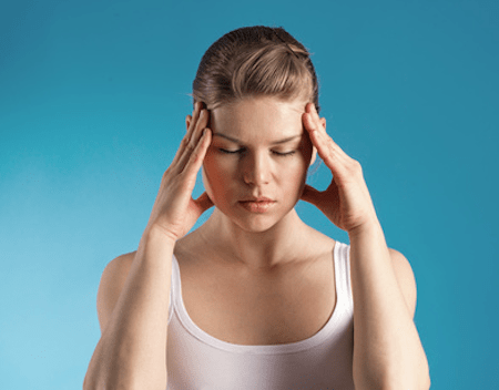 Woman having migraine headache is massaging her head