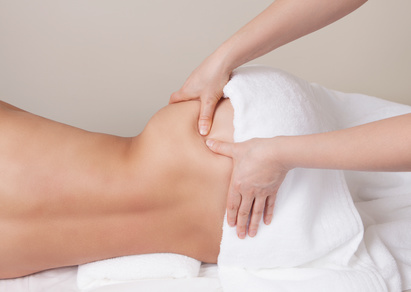 Massage therapist applying pressure point massage on a womans hip