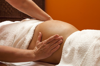 Pregnant woman receiving abdominal prenatal massage